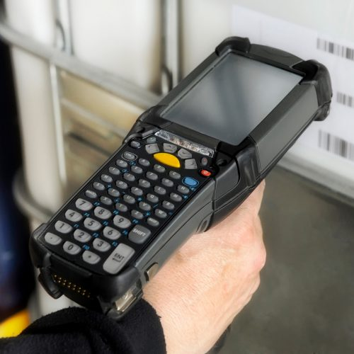 Person scanning a barcode with a handheld electronic scanner to identify a retail product or inventory and access the price and information on a digital readout